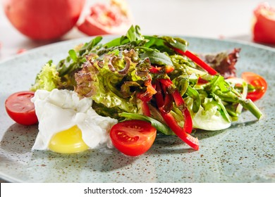 Macro Photo of mixed salad with poached egg, sliced sweet bell pepper, fresh lettuce leaves and cherry tomatoes. Restaurant starter menu with delicately cooked eggs and healthy salat close up