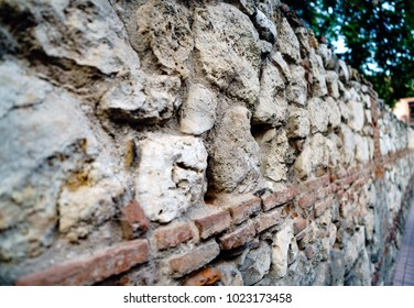 Macro photo of a Mozarabic stone wall with limestone eroded by time and old clay baked brick. very shallow depth of field