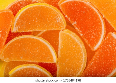 Macro photo multi-colored marmalade jelly candy's. Dessert marmalade in the form of lemon and orange slices. The sweetness of jelly candy yellow and orange.