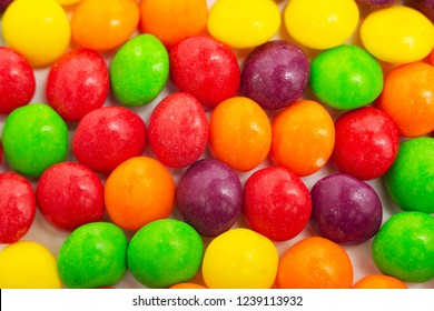 Macro photo of multicolored sweet candies in the glaze with peanuts inside in the form of a background, frames and colored inserts of candy
