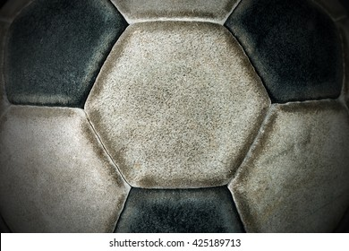 Macro photo of an old black and white soccer ball with hexagons and pentagons in leather
