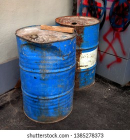 Macro photo of old blue barrels. Rusty metal barrels with peeling paint. Barrels stand in the gateway against the background of a wall painted with graffiti.