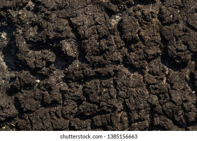 Macro photo of old embossed asphalt. Dark background texture. Contrast image of the asphalt surface relief with many protrusions, cracks and crevices and with dark shadows.