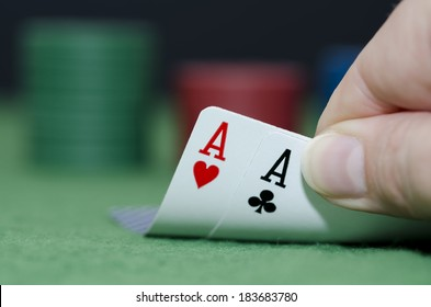 Macro photo of a pair of aces in the hand of a poker player, the focus is on the Aces the other tabs is blurred.