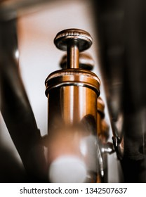 Macro photo of the piston valve of a trumpet. The finger button in framed by the lead pipe. Close up.