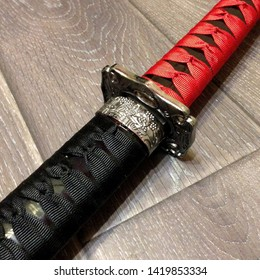 Macro photo red samurai katana sword. Japanese battle sword with a wicker handle. Traditional Fighting Japanese weapon - katana sword
