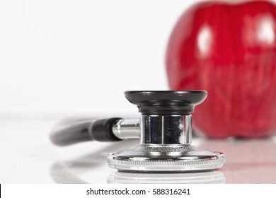 Macro photo of stethoscope and apple on white background.  Focus is on the stethoscope.