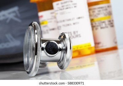 Macro photo of stethoscope, pill bottles and x ray.  Focus is on the stethoscope.