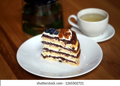 Macro photo of tasty cake with berries and tea on wooden table