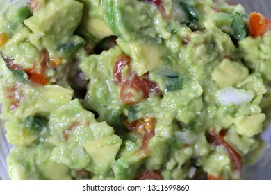 Macro photo of the texture of slightly chunky guacamole, a Mexican dip often eaten with crunchy nachos. Healthy and delicious food made of avocados, tomato, onion, garlic, cilantro, lime and spices.