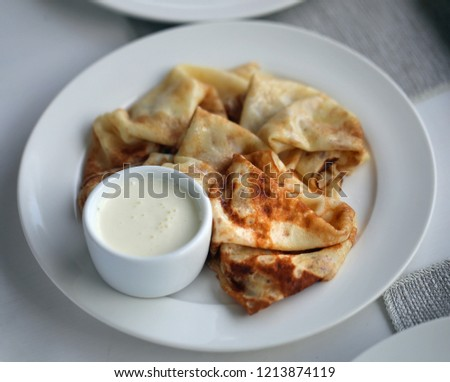 Macro photo of thin delicious pancakes with vanilla cream on a white plate