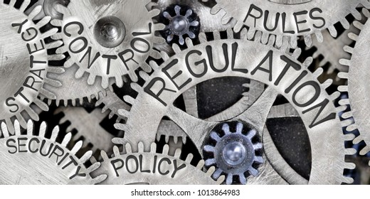 Macro photo of tooth wheel mechanism with REGULATION concept related words imprinted on metal surface