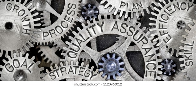 Macro photo of tooth wheel mechanism with QUALITY ASSURANCE concept related words imprinted on metal surface
