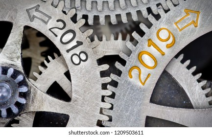 Macro photo of tooth wheel mechanism with numbers 2018, 2019 imprinted on clean metal surface; New Year concept