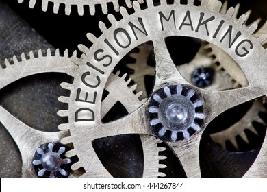 Macro photo of tooth wheel mechanism with DECISION MAKING concept letters