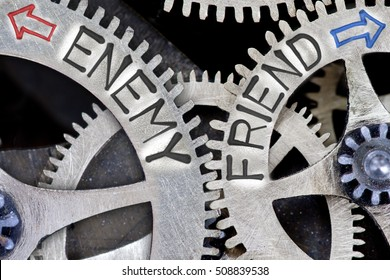 Macro photo of tooth wheel mechanism with arrows and ENEMY, FRIEND concept words