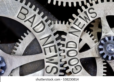 Macro photo of tooth wheel mechanism with imprinted BAD NEWS, GOOD NEWS concept words