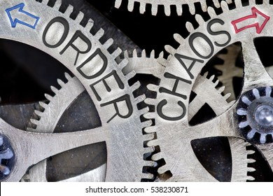 Macro photo of tooth wheel mechanism with imprinted arrows and ORDER, CHAOS concept words