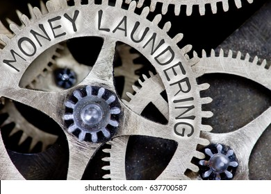 Macro photo of tooth wheel mechanism with MONEY LAUNDERING letters imprinted on metal surface