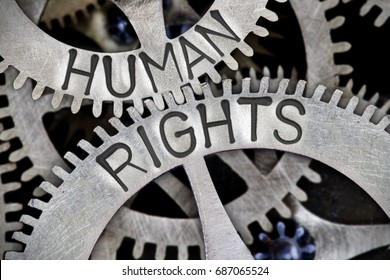 Macro photo of tooth wheel mechanism with HUMAN RIGHTS letters imprinted on metal surface