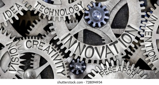 Macro photo of tooth wheel mechanism with INNOVATION, CREATIVITY, TECHNOLOGY, IDEA, VISION and RESEARCH words imprinted on metal surface