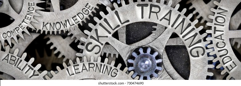 Macro photo of tooth wheel mechanism with SKILL TRAINING, EDUCATION, LEARNING, ABILITY, KNOWLEDGE and COMPETENCE words imprinted on metal surface