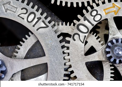 Macro photo of tooth wheel mechanism with numbers 2017, 2018 imprinted on clean metal surface; New Year concept