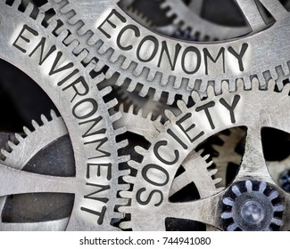 Macro photo of tooth wheel mechanism with ECONOMY, SOCIETY and ENVIRONMENT; concept of SUSTAINABILITY