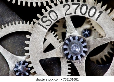 Macro photo of tooth wheel mechanism with ISO 27001 imprinted on metal surface