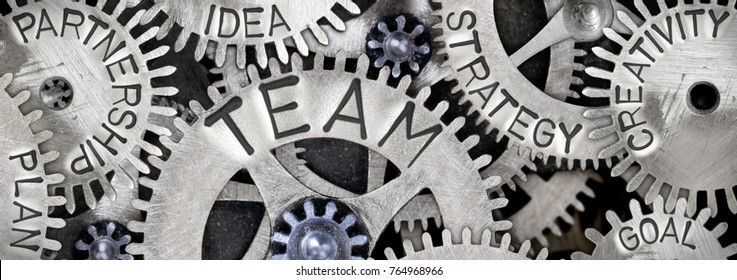 Macro photo of tooth wheel mechanism with TEAM concept related words imprinted on metal surface