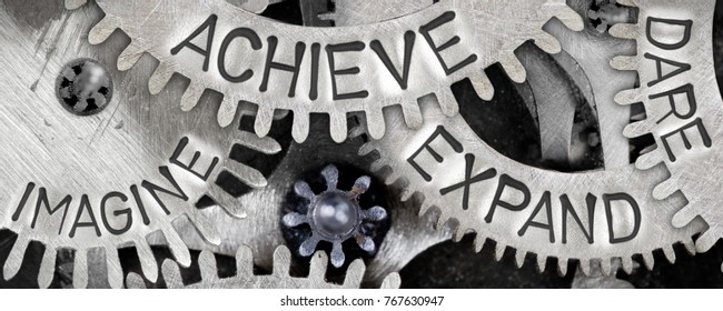 Macro photo of tooth wheel mechanism with IMAGINE, DARE, EXPAND, ACHIEVE words imprinted on metal surface; concept of IDEA
