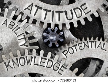 Macro photo of tooth wheel mechanism with ATTITUDE, ABILITY, KNOWLEDGE and POTENTIAL words imprinted on metal surface