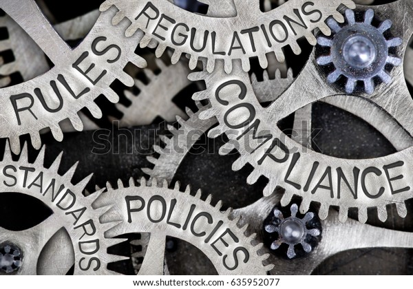Macro photo of tooth wheels with COMPLIANCE, REGULATIONS, STANDARDS, POLICIES and RULES words imprinted on metal surface