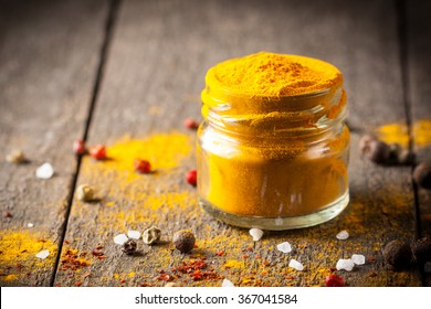 Macro photo of turmeric powder with spices. Yellow curry.