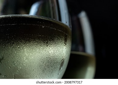 macro photo of two glasses of white wine. Two glasses with chilled wine in it and condensation