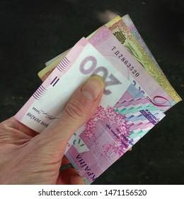 Macro photo of Ukrainian hryvnia in hand. Texture background Ukrainian bills money hryvnia in hand. Image of money 100 and 200  UAH hryvnia bill in hand