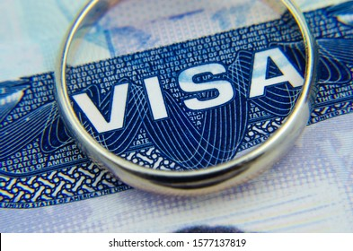 Macro photo of US entry visa sticker in a passport and a ring. Conceptual photo for fiancee visa and immigration. Selective focus.
