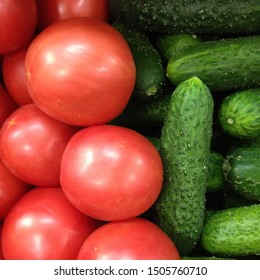 Macro photo of a vegetable red tomato and green cucumbers. Fruit vegetables tomatoes and cucumbers. Background of pink tomatoes with green cucumbers