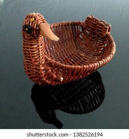Macro photo of a wicker basket. Basket in the form of a duck. Duck-basket bread box on a black glass table.
