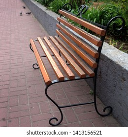 Macro photo of a wooden bench. Texture background urban landscape bench with wrought iron legs. wooden garden bench in the city on the background of nature