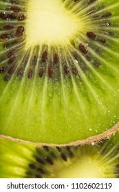 Macro photograph of kiwifruit slices.
