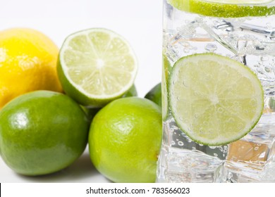 Macro photograph of lemon and lime with glass of refreshing drink.