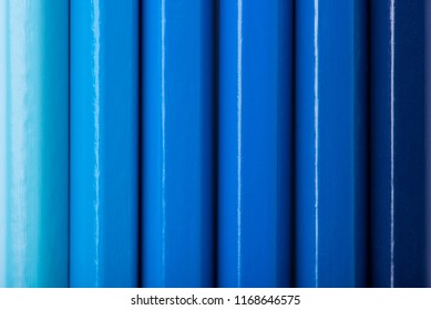 Macro photograph of several sharpened pencils of blue color on a white background