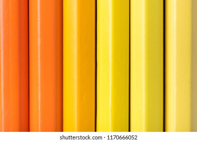 Macro photograph of several sharpened pencils of yellow and orange color on a white background