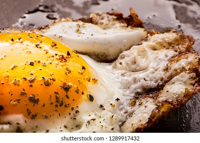 A macro photograph of a single fried egg, sunny side up cooked in a frying pan.  Ground pepper coving the egg and yellow egg yoke.