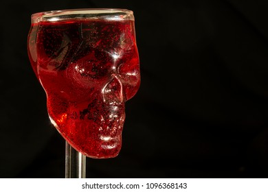 Macro photograph of a skull glass. Red liquid mimics blood.