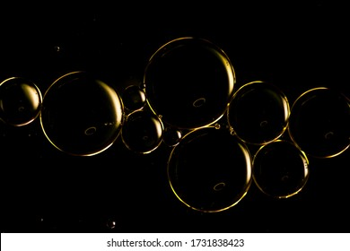 A macro photograph of water droplets on oil