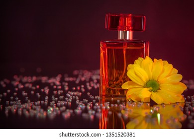 Macro photography of a bottle of perfume standing on a mirror near a beautiful yellow flower among rhinestones. Studio photography close up on a black background, using red backlighting.