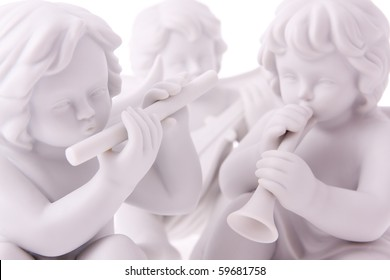 Macro photography of isolated porcelain figurines of angels playing musical instruments.