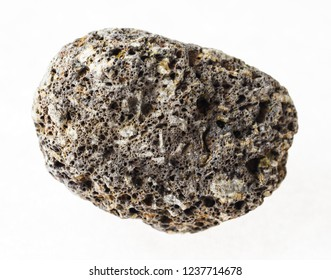 macro photography of natural mineral from geological collection - pebble from pumice stone on white background